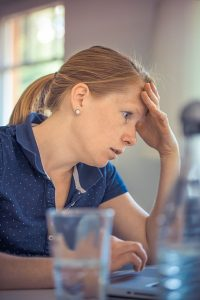 woman stressed at her computer over finances